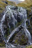 NEW ZEALAND, Fiordland National Park. Waterfall with quartz vein, Merrie Range.
