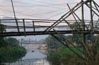 LAOS, Vientiane, Vang Vieng. Rickety bridge over channel of Nam Song river.