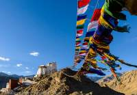 Buddhist prayer flags and Tsemo Gompa, monastery/fort on hilltop overlooking Leh city. Sunset.