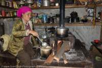 Woman in kitchen, with wood-fired stove, Manaslu Circuit, Gorkha, Nepal