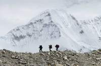 NEPAL. Trekkers descending moriane crest in upper Honku valley, Makalu - Barun National Park.