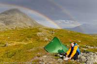 NORWAY, Troms, Lyngsalpan (Lyngen Alps). Rainbow over Lomvatnan lakes, with camp.