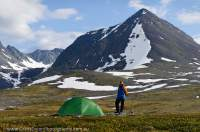 NORWAY, Troms, Lyngsalpan (Lyngen Alps). Hiker camped at Lomvatnan lakes, Kaulddalen valley & peaks beyond.