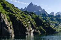 NORWAY, Nordland. Lofoten Islands, Austvagoy. Trolltinden peak towers above glaciated gneiss ridges in Trollfjord.