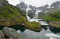 NORWAY, Nordland. Lofoten Islands, Austvagoy. Peak & glacial lake above Trollfjord, with remnant winter ice